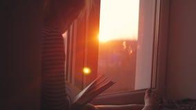 Un adolescente de la niña que se imagina historia con el libro en la ventana abierta en travesaño en fondo de la puesta del sol L almacen de video