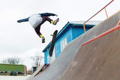 Un adolescente del skater en un sombrero hace un truco con un salto en la rampa Un skater está volando en el aire Imagen de archivo libre de regalías