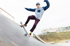 Un adolescente del skater en un sombrero hace un truco con un salto en la rampa Un skater está volando en el aire Foto de archivo