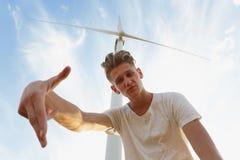 Un adolescente descarado en un fondo del cielo azul Primer del individuo elegante del inconformista al lado de un molino de vient Imagenes de archivo
