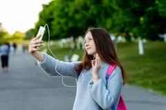 Un adolescente después de la escuela En parque del verano en la calle En sus manos sostiene un smartphone Comunique por el teléfo Fotografía de archivo libre de regalías