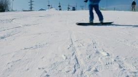 Un adolescente di 12 anni in panno blu che fa scorrere su uno snowboard dal parco seguente della città di liftin del cielo di dis video d archivio