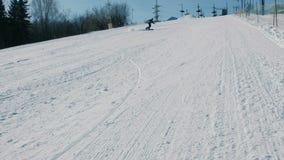 Un adolescente di 12 anni in panno grigio che fa scorrere su uno snowboard dall'ascensore seguente del cielo di discesa della nev video d archivio