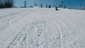 Un adolescente di 12 anni in panno grigio che fa scorrere su uno snowboard dalla discesa della neve nel parco della città archivi video