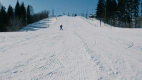 Un adolescente di 12 anni in vestito blu che fa scorrere su uno snowboard dall'ascensore seguente del cielo di discesa della neve video d archivio