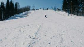 Un adolescente di 12 anni in vestito blu che fa scorrere su uno snowboard dall'ascensore seguente del cielo di discesa della neve stock footage
