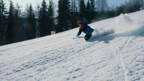 Un adolescente di 12 anni in vestito blu che fa scorrere su uno snowboard a partire dall'ascensore e dalle cadute prossimi del ci stock footage