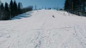 Un adolescente di 12 anni in vestito grigio che fa scorrere su uno snowboard dall'ascensore seguente del cielo di discesa della n stock footage