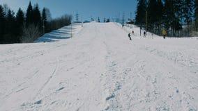 Un adolescente di 12 anni in vestito grigio che fa scorrere su uno snowboard dall'ascensore seguente del cielo di discesa della n archivi video