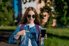 Un adolescente en un día soleado brillante con las gafas de sol En el verano en el parque en el aire fresco En sus manos sostiene Fotografía de archivo libre de regalías