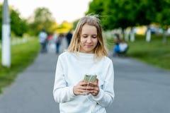 Un adolescente En el verano en ciudad En sus manos sostiene un smartphone Escucha el vídeo de observación de la música en Interne Imagen de archivo
