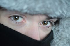 Un adolescente en un sombrero de piel y una cara cubiertos con una bufanda Imagenes de archivo