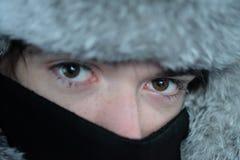 Un adolescente en un sombrero de piel y una cara cubiertos con una bufanda Fotografía de archivo