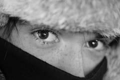 Un adolescente en un sombrero de piel y una cara cubiertos con una bufanda Fotos de archivo