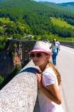 Un adolescente en un sombrero y vidrios en el puente que mira hacia fuera en la distancia contra la perspectiva de las montañas Fotografía de archivo