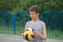 Un adolescente en un chaleco sostiene una bola en su mano Imagenes de archivo