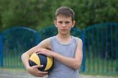 Un adolescente en un chaleco sostiene una bola en su mano Foto de archivo