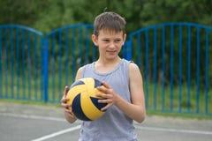 Un adolescente en un chaleco sostiene una bola en su mano Imagen de archivo libre de regalías