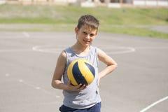 Un adolescente en un chaleco sostiene una bola en su mano Imagen de archivo