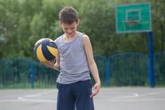 Un adolescente en un chaleco sostiene una bola en su mano Imágenes de archivo libres de regalías