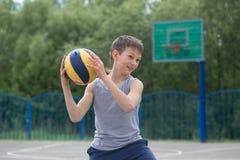 Un adolescente en un chaleco sostiene una bola en su mano Fotos de archivo libres de regalías