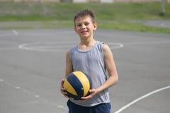 Un adolescente en un chaleco sostiene una bola en su mano Fotos de archivo