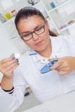 Un adolescente en un laboratorio de la escuela en la química, haciendo experimenta en laboratorio Foto de archivo