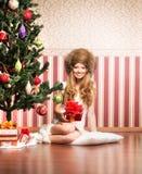 Un adolescente en un sombrero que se sienta cerca del árbol de navidad Fotos de archivo