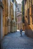Un adolescente en una bicicleta está montando a lo largo de las calles viejas de Padua, Italia Fotos de archivo