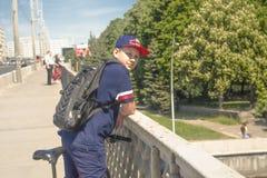 Un adolescente en una camiseta azul se coloca en el bridge6 imágenes de archivo libres de regalías