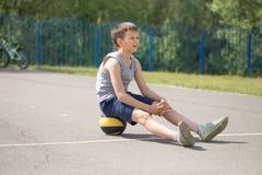 Un adolescente en una camiseta se está sentando en una reclinación de la bola Imágenes de archivo libres de regalías