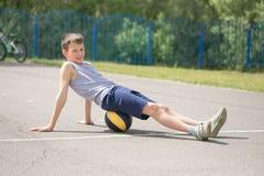 Un adolescente en una camiseta se está sentando en una reclinación de la bola Imagen de archivo libre de regalías