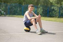 Un adolescente en una camiseta se está sentando en una reclinación de la bola Fotografía de archivo