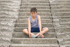 Un adolescente en una camiseta se sienta en pasos concretos Fotos de archivo