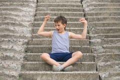 Un adolescente en una camiseta se sienta en pasos concretos Fotos de archivo libres de regalías
