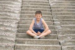 Un adolescente en una camiseta se sienta en pasos concretos Imagen de archivo