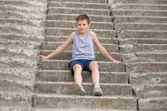 Un adolescente en una camiseta se sienta en pasos concretos Imágenes de archivo libres de regalías