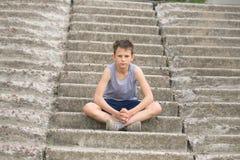 Un adolescente en una camiseta se sienta en pasos concretos Imagenes de archivo