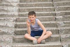 Un adolescente en una camiseta se sienta en pasos concretos Foto de archivo libre de regalías