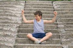 Un adolescente en una camiseta se sienta en pasos concretos Fotografía de archivo