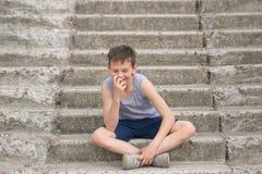 Un adolescente en una camiseta se sienta en pasos concretos Foto de archivo