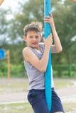 Un adolescente en una camiseta sube en un polo gimnástico Imagen de archivo