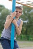 Un adolescente en una camiseta sube en un polo gimnástico Foto de archivo