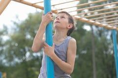 Un adolescente en una camiseta sube en un polo gimnástico Imagen de archivo libre de regalías