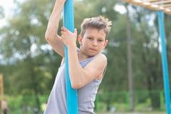 Un adolescente en una camiseta sube en un polo gimnástico Imagenes de archivo