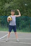 Un adolescente en una camiseta y pantalones cortos celebra la victoria Imágenes de archivo libres de regalías