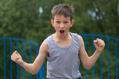 Un adolescente en una camiseta y pantalones cortos celebra la victoria Imagen de archivo libre de regalías