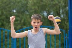 Un adolescente en una camiseta y pantalones cortos celebra la victoria Fotografía de archivo