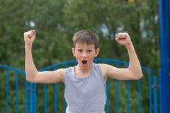 Un adolescente en una camiseta y pantalones cortos celebra la victoria Fotos de archivo