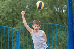 Un adolescente en una camiseta y pantalones cortos celebra la victoria Foto de archivo